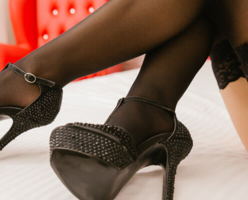Detail of sexy legs with black lace-top stockings and high heels; MarriageHeat