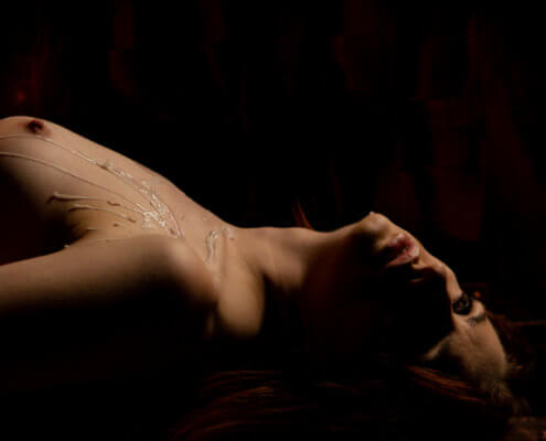 Hot wax drips on a woman's bare chest; MarriageHeat