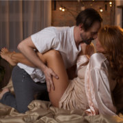 Passionate man and woman on bed; MarriageHeat