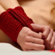 Woamn's hands bound at the wrist with red silk rope ~ MarriageHeat