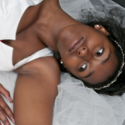 Young black woman in wedding dress relaxing on bed