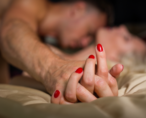 Wife squirms on bed as husband kisses neck and lower. MarriageHeat